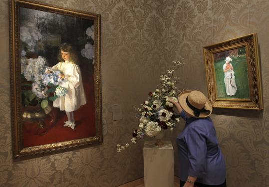 Marisa McCoy of the Wareham Garden Club prepares her Art in Bloom arrangement near John Singer Sargent's 1895 portrait of Helen Sears.