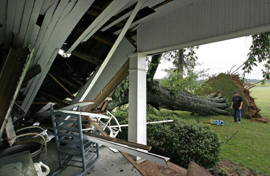 Karl Rhodes looked at the damage to a house in Florence, Ala., after storms caused a large tree to fall Tuesday.