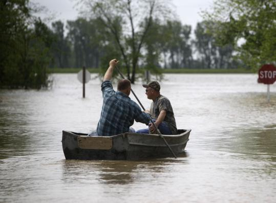 People in Commerce, Mo., turned to rowboats yesterday as powerful storms in the middle of the country have caused rivers to overflow and threaten several Missouri towns.