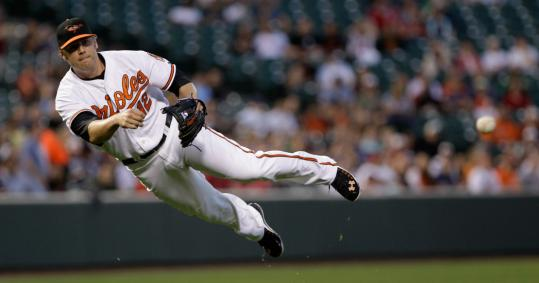 Orioles third baseman Mark Reynolds makes an acrobatic play to retire Dustin Pedroia.