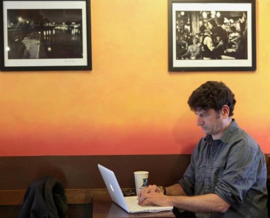 Larry Mayer searched through job listings at Darwin's coffee shop in Cambridge. He has been hunting for work since moving back to Boston from the West Coast.