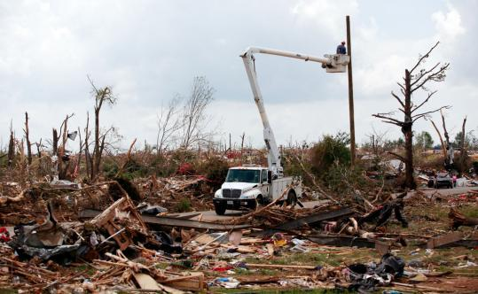 Workers replaced a destroyed utility pole yesterday in Holt, Ala., one of the hardest hit of seven states last week by a spree of tornadoes that flattened homes and killed 342 people.