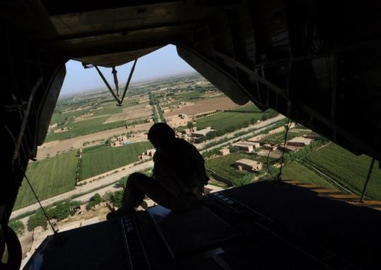 A US Marine helicopter crewman looked out at the Marjah district yesterday, a day after Osama bin Laden's killing.