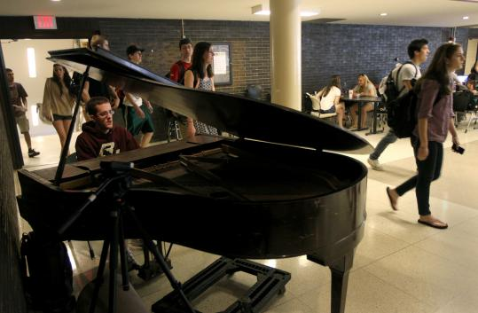 Dennis Carr, in a weekday routine he started as a BC freshman, plays tunes for the lunch crowd in the Eagle's Nest in McElroy Commons.