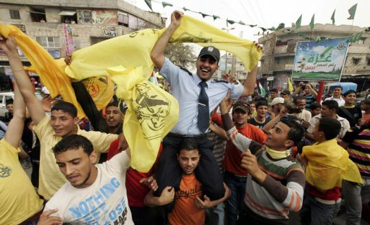 A Hamas policeman held up the Fatah flag yesterday during celebrations to mark the groups' reconciliation agreement.