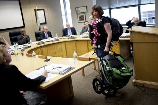 Amber Baker showed the MBTA board of directors how she would fold her stroller while holding her daughters, Rose, 19 months, and Ella, 2 months.