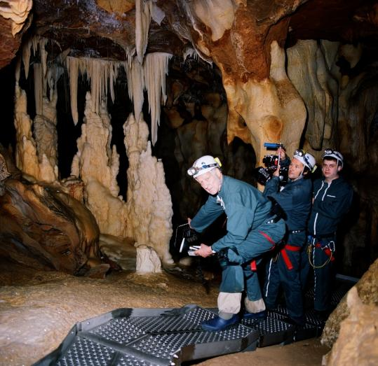 Werner Herzog (white hat) and his crew film in the Chauvet-Pont-d'Arc cave in southern France, site of the oldest Paleolithic cave paintings ever found. They were allowed to film for only six days, and for only four hours each day.