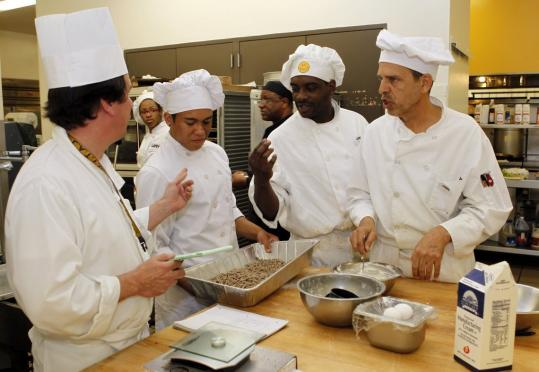 Chef Jerry Vachon (left) worked with culinary arts students Los Angeles Trade-Technical College in Los Angeles yesterday. The students' job outlook dimmed with the latest economic report.