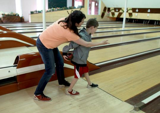 Nicole Mela showed her son Ryan some of the finer points of the lane game at Fairway Bowling in Natick. The bowling establishment is shutting down after 56 years of operation.