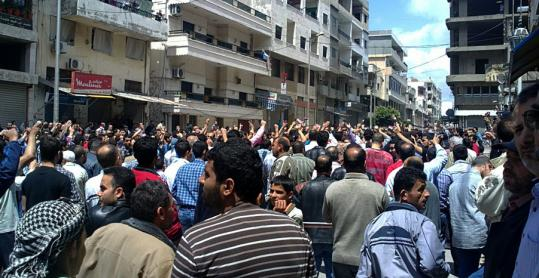 In this photo, taken on a mobile phone by a citizen journalist, antigovernment protesters demonstrated in Banias on Friday. Syrian troops took up positions in the coastal town yesterday.