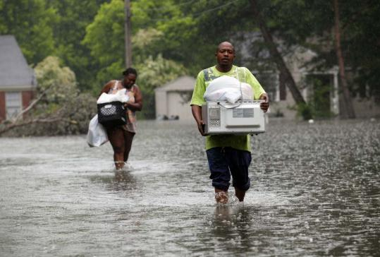 Jonathan White and Leandra Felton waded through slowly rising flood waters with items from their home in Memphis, as the Mississippi River reached near-record levels.