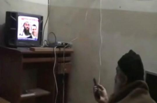 In this video, Osama bin Laden sat on the floor in a small room, wrapped in a blanket as he watched news clips about himself.