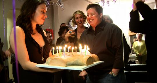 "Chaz Bono (center) is presented with a cake by his girlfriend, Jenny Elia (left), in ""Becoming Chaz,'' a documentary of Bono's gender reassignment."