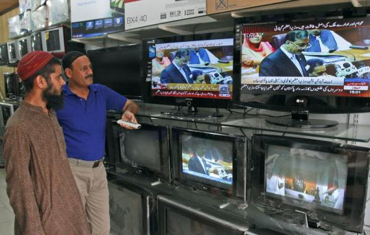 Pakistanis in Karachi watched the prime minister, Yousaf Gilani, address Parliament yesterday. Gilani denied allegations that Pakistan was complicit in protecting Osama bin Laden.