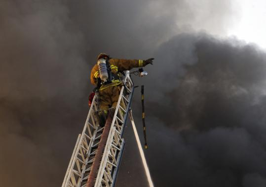 A firefighter stood atop a ladder battling a fire feeding on soybean oil at a frozen Chinese food plant yesterday in Huntington Park, Calif., that took 100 firefighters six hours to extinguish.