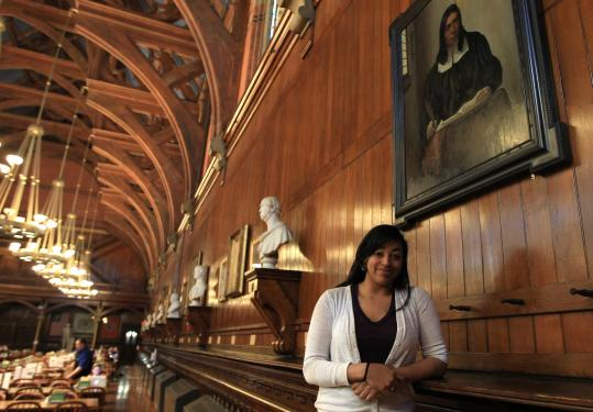 Tiffany Smalley at Harvard beneath a portrait of Caleb Cheeshahteaumuck, her Wampanoag predecessor.