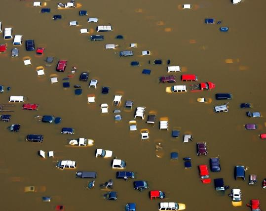 Cars stood inundated yesterday in Memphis near the overflowing Wolf River, a tributary to the Mississippi. The flooding moving downriver put Delta farmland and homes in jeopardy.