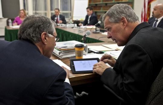 In North Reading, finance director Joe Tassone (left) and Town Administrator Greg Balukonis use an iPad during a selectmen's meeting.