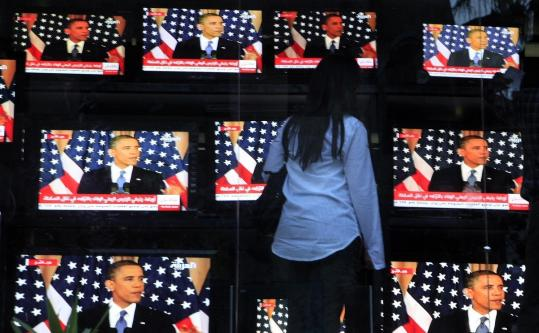 An Egyptian woman watches President Obama's policy address yesterday while outside a shop selling televisions in Cairo.