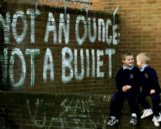 Catholic schoolchildren play near graffiti supporting the Irish Republican Army in Belfast, Northern Ireland, in, 2000.
