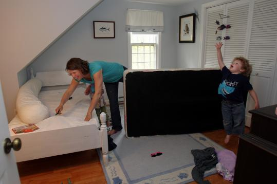 Megan Harden prepared twin beds in a children's room of her East Sandwich home last week for summer renters.