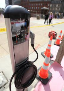 The electric car charging stations on Cambridge Street in Boston have an 11-foot-long power cord coiled neatly at the front. Drivers can recharge their gas-free vehicles there for the cost of feeding the parking meter.