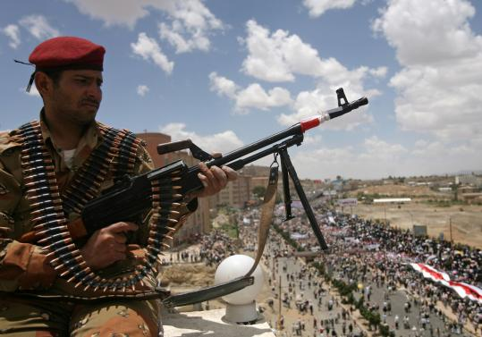 A Yemeni soldier who defected to the opposition watched an antigovernment protest yesterday in the capital, Sana.