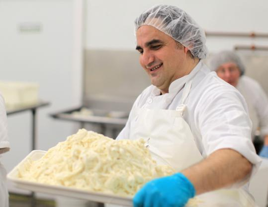 Domenico Marchitelli, hired from Italy to make Maplebrook Farm's burrata in Bennington, Vt., carries a tray of stratchiatella.