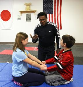 Larry Garron teaches self-defense to 10-year-old Sophia Dimidis and her brother William, 8.