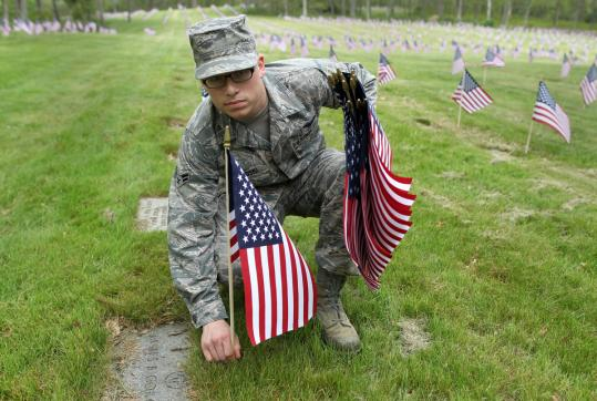 Airman First Class Wesley Golanoski placed flags at the Massachusetts National Cemetery in Bourne. The policy against placing flags at graves was changed after Paul Monti, who lost his son, fought to do so.