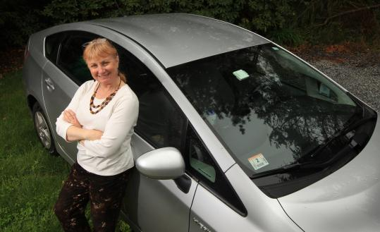 "Westwood's Claire Sullivan and her Toyota Prius, which gets 50 miles a gallon. ""I love it,'' she says. ""I only go to the gas station every couple of weeks.''"