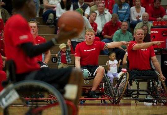 Jese Schag (center) and Travis Greene (far right) of the Marine Corps wheelchair basketball team yell instructions to teammate Keith Buckmon at the Warrior Games.
