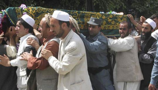 Mourners carried the coffin yesterday of a north Afghanistan senior police commander killed by a suicide bomber Saturday. NATO is investigating a report that its bombs killed a group of sleeping women and children in a village in Helmand Province.