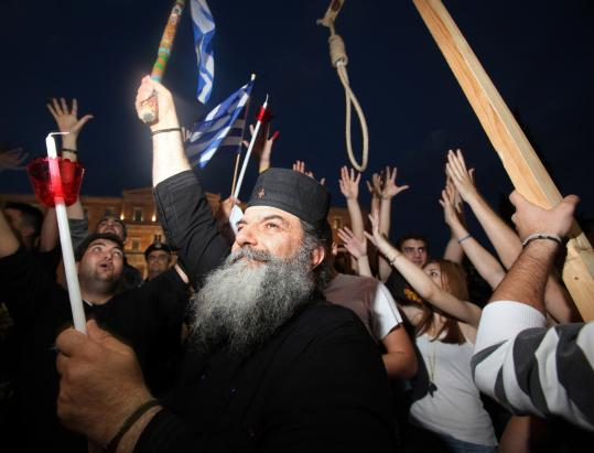 Protesters attended a rally against new austerity measures in front of Parliament in Athens. The wage cuts and tax increases under Greece's bailout have led to strikes.