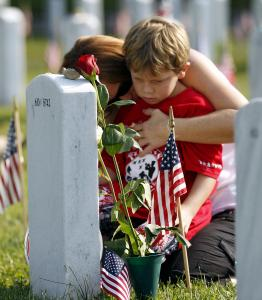 Trisha Lawton and her son Caden prayed at the grave of their husband and father, Marine Captain Garrett T. Lawton, in Arlington National Cemetery yesterday.