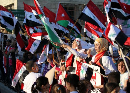 Syrian protesters carried national flags as they demanded that President Bashar Assad step down, during a sit-in near the Syrian Embassy in Amman, Jordan, yesterday.