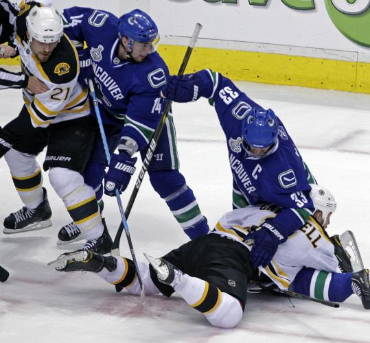 Canucks captain Henrik Sedin strong-arms the Bruins' Gregory Campbell, while Alex Burrows and Boston's Andrew Ference look for the puck.