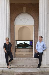 "Jennifer Allora and Guillermo Calzadilla outside the US pavilion at the Venice Biennale, with their work ""Armed Freedom Lying on a Sunbed'' seen inside."