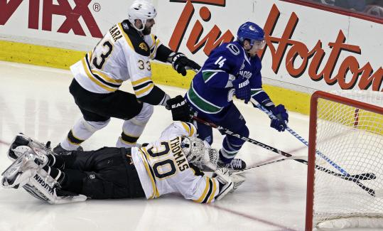 Vancouver's Alex Burrows swings around the Bruins' net en route to his winning goal as Tim Thomas and Zdeno Chara (33) attempt to break up the play.