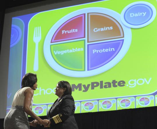 Michelle Obama greets Surgeon General Regina M. Benjamin as they introduce the MyPlate initiative.