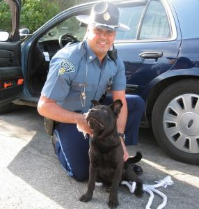 Trooper Brian Pearl, who works out of Sturbridge, with Shadow, the puppy he pulled from tornado rubble in Monson.