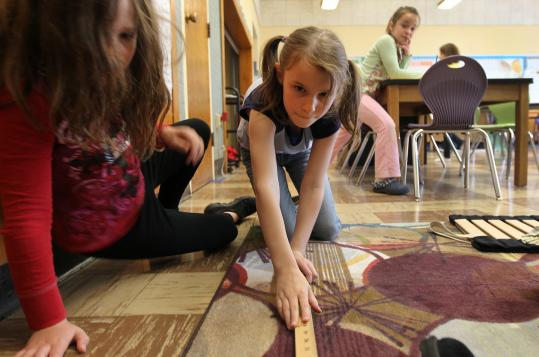Janice Tabin (above, from left), Greta Risgin, and Lydia Mroz work on a scale drawing of their grade 2-to-4 classroom at Anova School in Melrose.