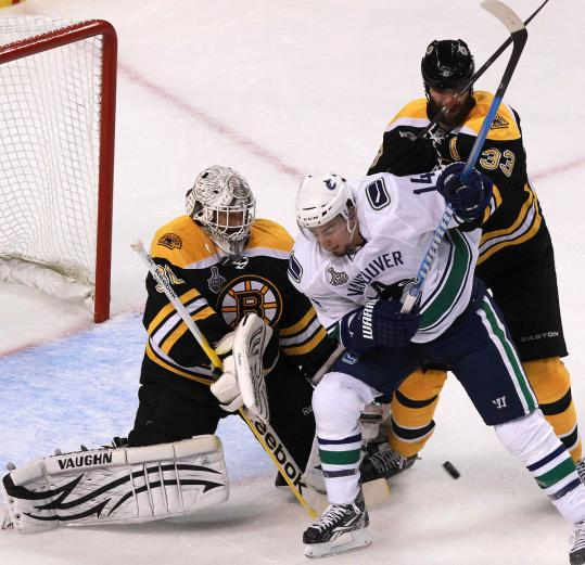 Bruins Tim Thomas (left) and Zdeno Chara rattle Vancouver's Alex Burrows as they snuff out this scoring attempt.