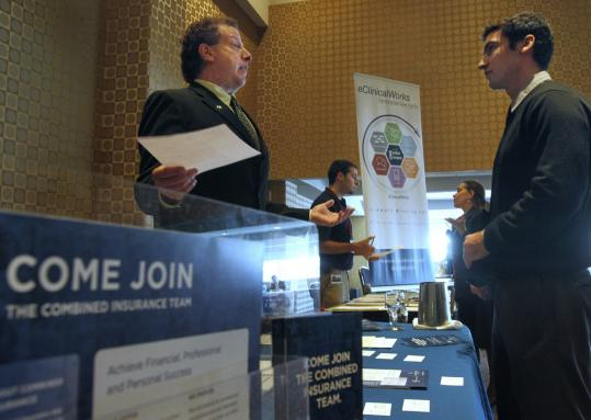 Mitchell Orenstein, of Combined Insurance (left) chatted with Gabriel Moraga of Somerville at a job fair in Boston this week. The US unemployment rate has edged up to 9.1 percent.