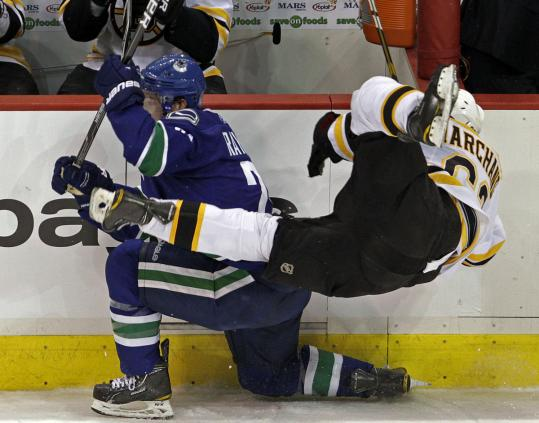 Brad Marchand is usually flying around the ice for the Bruins, although this time the flight is courtesy of Canucks forward Mason Raymond's sturdy check.