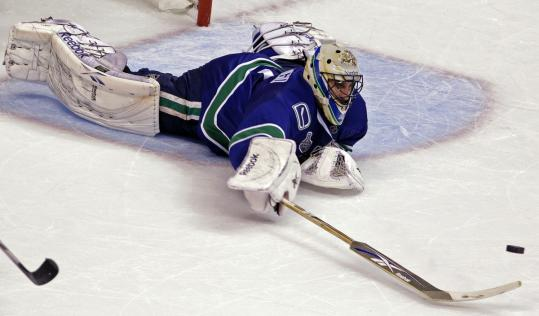Canucks goalie Roberto Luongo goes all-out to knock a puck out of harm's way in the second.