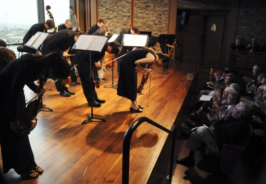 Members of A Far Cry, a self-conducted string orchestra, take a bow Sunday at the Shalin Liu Performance Center in Rockport.