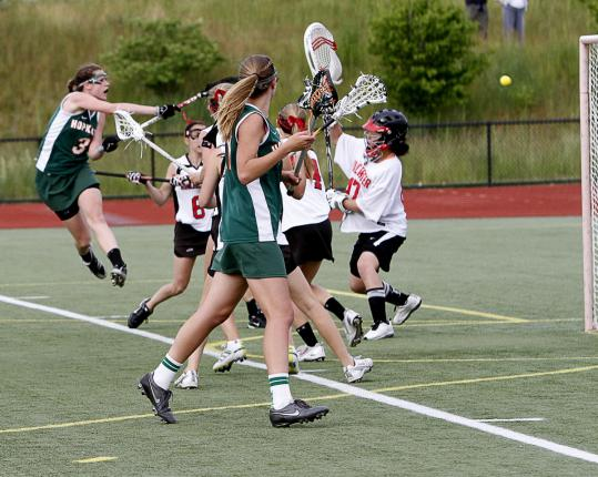 Hopkinton's Tess Chandler leaps and fires a shot into the Winchester net for one of her seven goals.