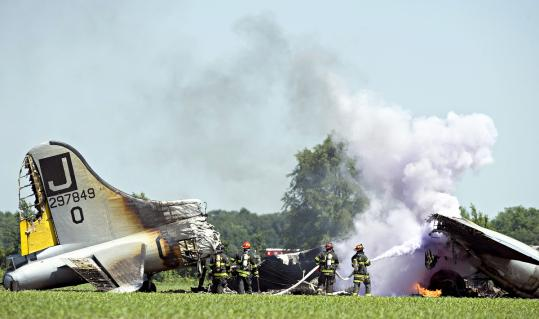 Firefighters extinguished flames after a B-17 bomber burned following an emergency landing in a cornfield in Oswego, Ill., yesterday. The accident happened shortly after the plane took off from Aurora Municipal Airport.