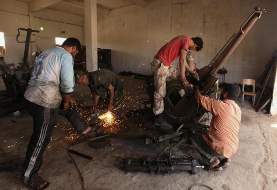 At a workshop in Benghazi yesterday, rebel soldiers repaired weapons captured from forces loyal to Libyan leader Moammar Khadafy. Such arms are bolstering opposition forces.